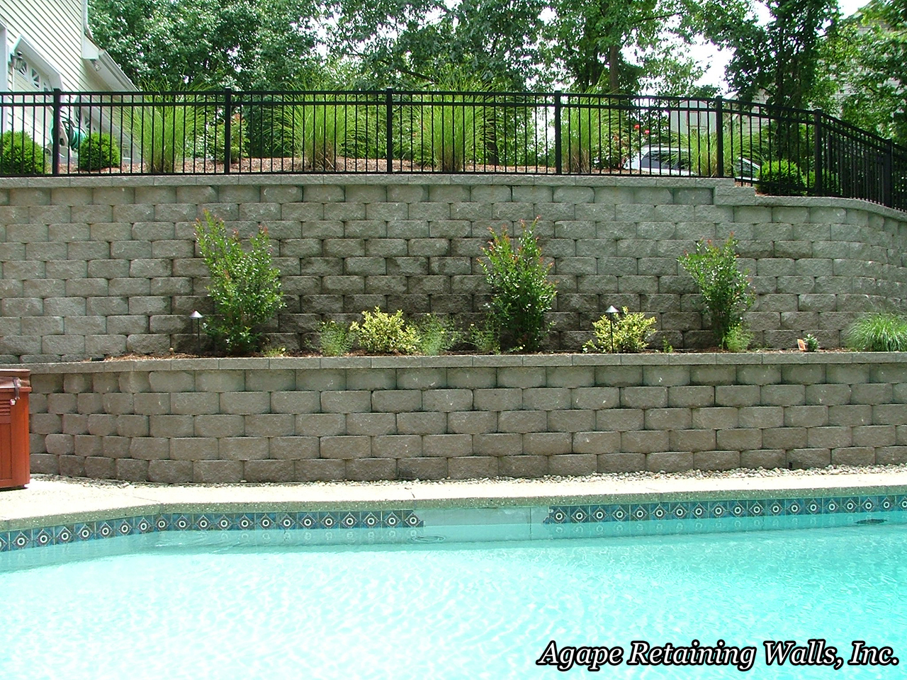 the terraced retaining wall design allowed the landscape contractor to come in after us and break up the look of this large retaining wall with some great